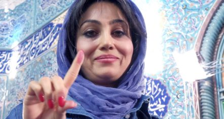 Iranian woman shows her ink-stained finger after casting her vote during elections for the parliament and Assembly of Experts, in Tehran